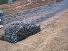 Filling of the gabions with basaltic lava coarse gravel